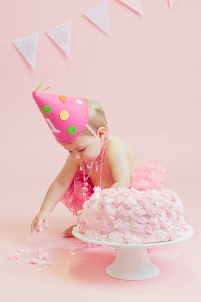 Baby girl with pink cake