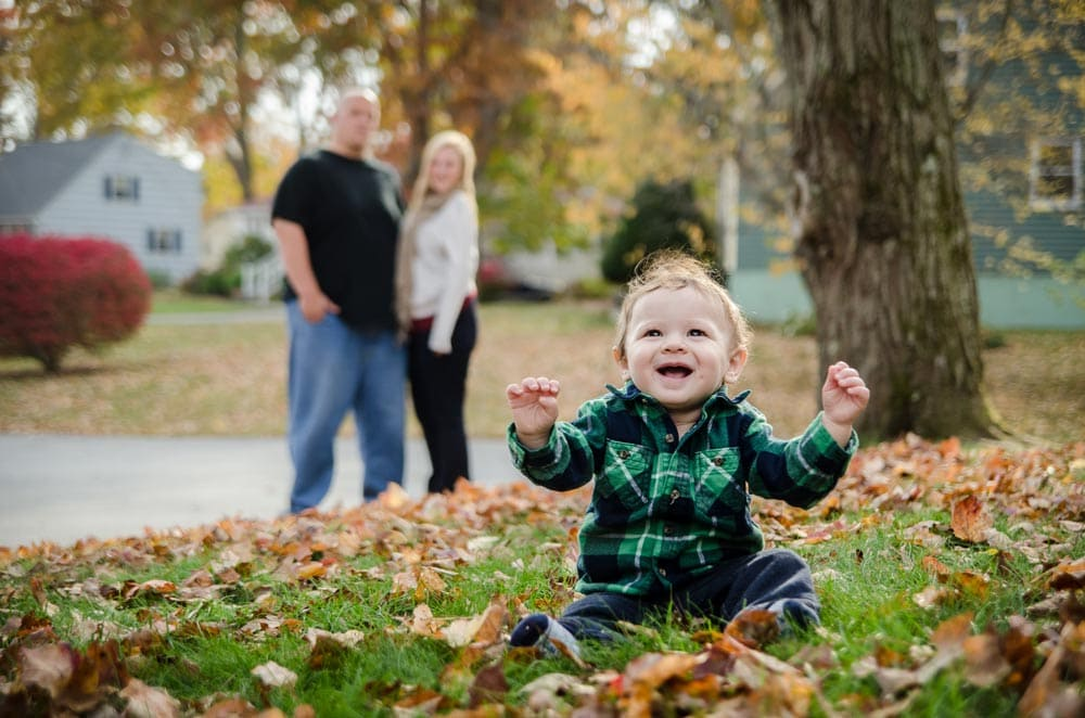 baby boy laughing with parents on background