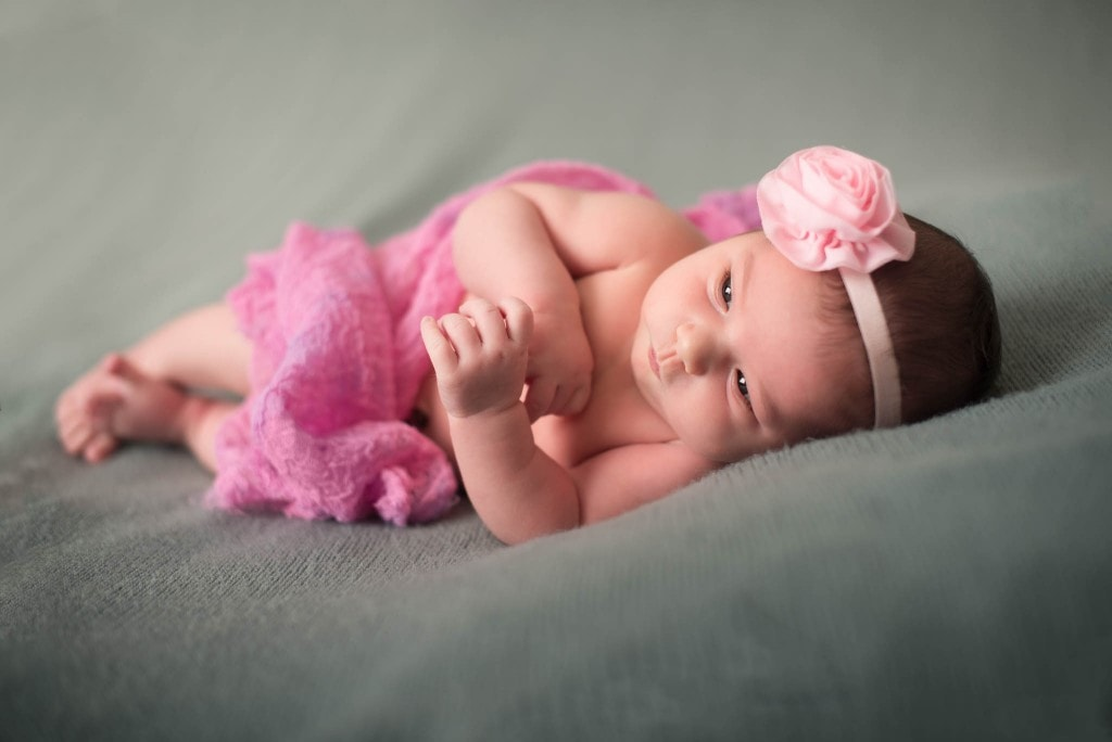 baby in pink laying donw on bed
