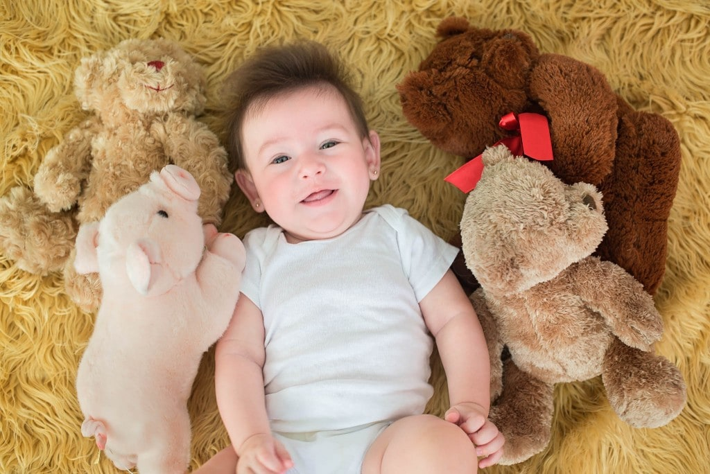 baby and stuffed animals friends laying down on fur