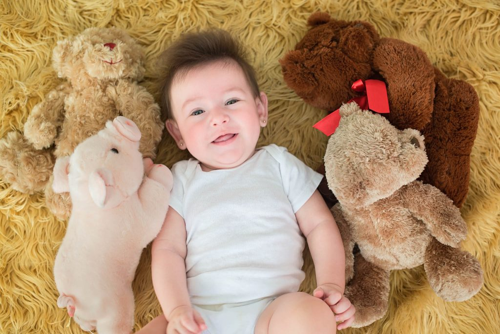 baby with stuffed animals laying down on the floor