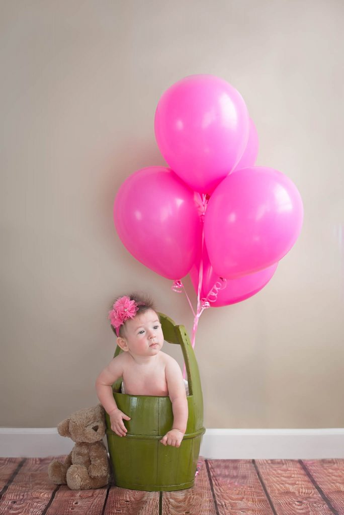 baby on green bucket with pink ballons