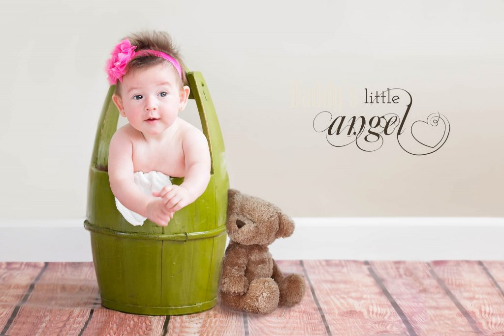 baby in a green bucket with bear toy