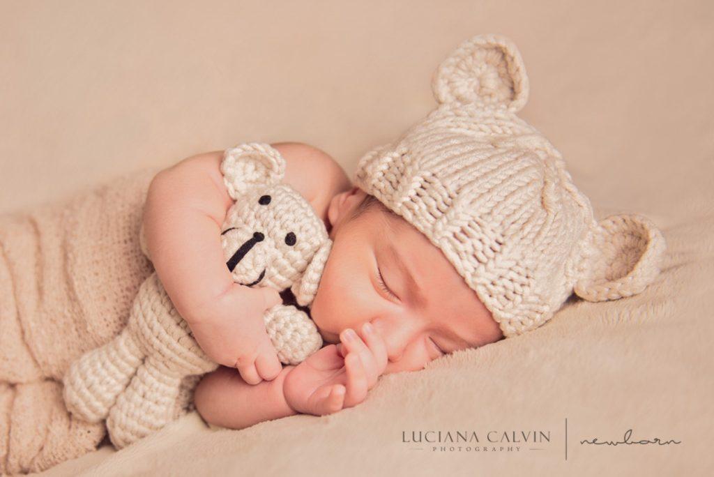 newborn sleeping with a little stuffed animal