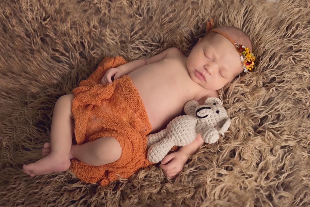 newborn sleeping with a little bear