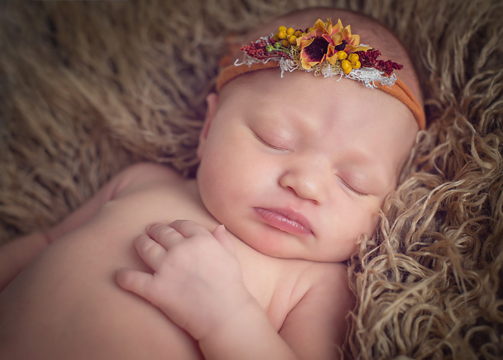 newborn with orange headband sleeping