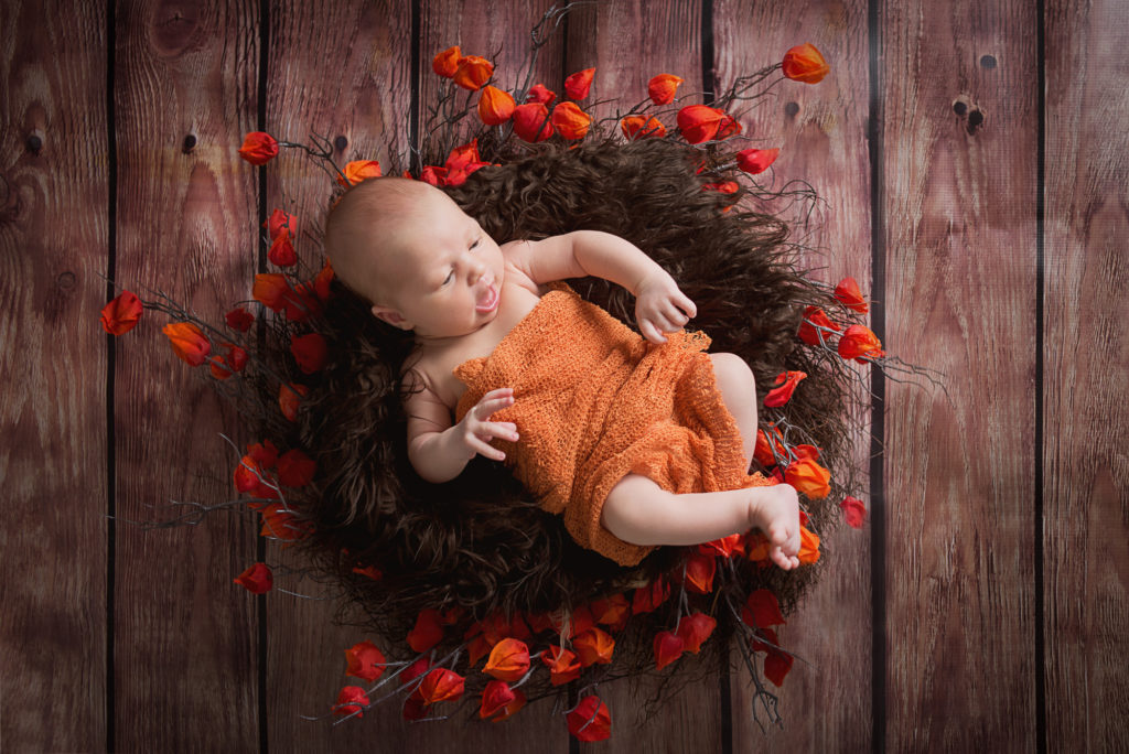 newborn laying in a basket with flowers