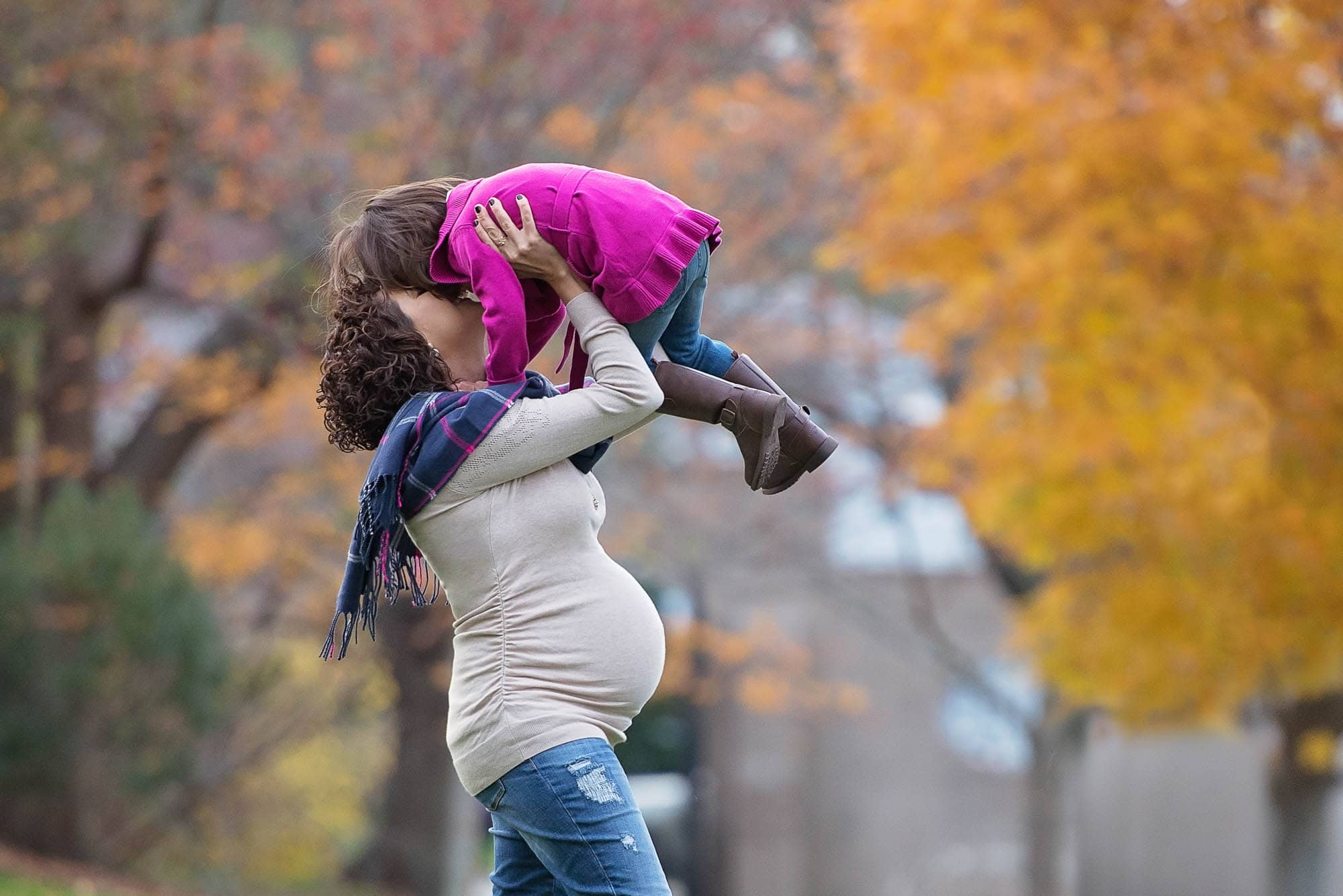 pregnant mother and daughter kissing